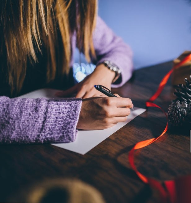 Beautiful young woman writing a Christmas card