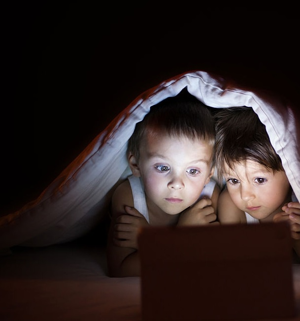 Two brothers enjoying a children's story before bedtime.