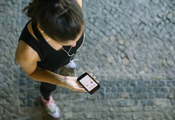 Top view shot of woman training outdoors and using a smartphone to monitor her fitness progress.