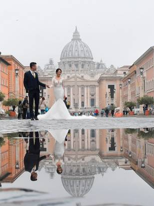 A groom and a bride pose for photos with St Peter's basilica in the background on May 9, 2018 in Rome. (Photo by Tiziana FABI / AFP) (Photo credit should read TIZIANA FABI/AFP/Getty Images)
