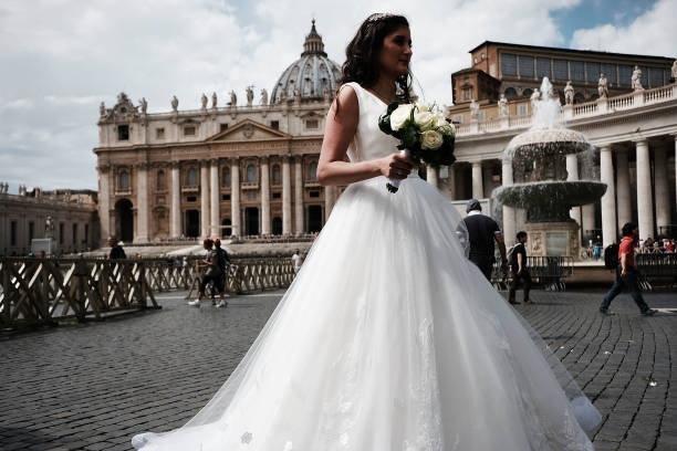 VATICAN CITY, VATICAN - SEPTEMBER 01: A bride pauses in St. Peter's Square on September 01, 2018 in Vatican City, Vatican. Tensions in the Vatican are high following accusations that Pope Francis covered up for an American ex-cardinal accused of sexual misconduct. Archbishop Carlo Maria Vigano, a member of the conservative movement in the church, made the allegations and has called for Pope Francis to resign. Many Vatican insiders see the dispute as an outgrowth of the growing tension between the left leaning Pope and the more conservative and anti-homosexual faction of the Catholic Church. (Photo by Spencer Platt/Getty Images)