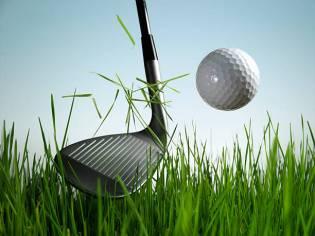 gold club strking ball in grass