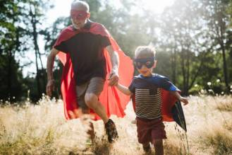 A senior man has fun dressing up in a hero mask and cape costume with his grandchild, a boy about 4 years old. They have fun playing a running around in a sunny grassy field.