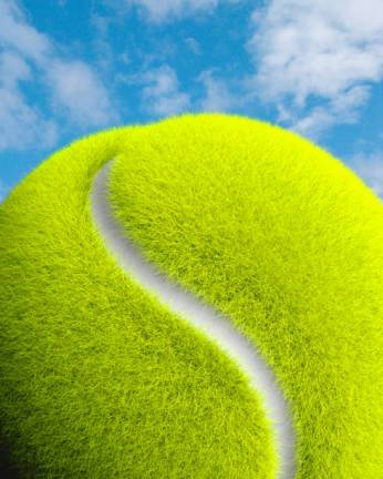 Tennis ball close up with a blue sky in the background. A hill with a path leading through the grass.