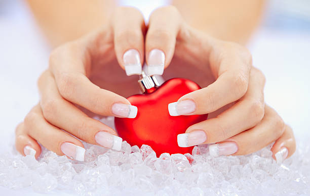 Beautiful woman's hands around christmas heart.