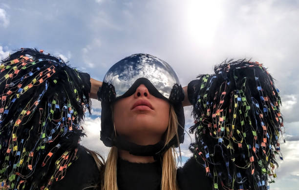 woman with ski helmet and goggles is looking up into the sky, fashion pullover