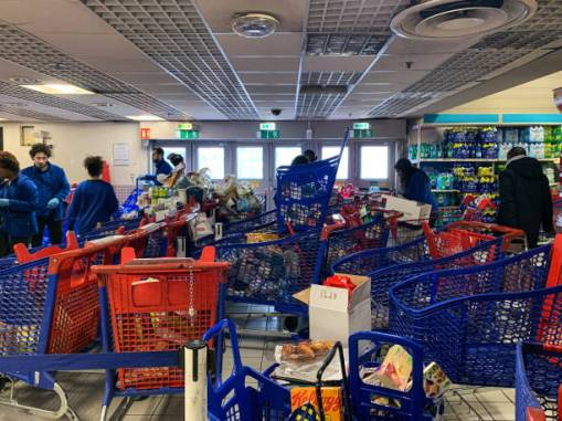 Customers are wearing masks and gloves to do their shopping in a supermarket Carrefour de Creteil in Paris, France, on March 15, 2020, as the COVID-19 coronavirus epidemic intensifies in France. The Prime Minister has announced the closure of all non-essential shops. (Photo by Samuel Boivin/NurPhoto via Getty Images)