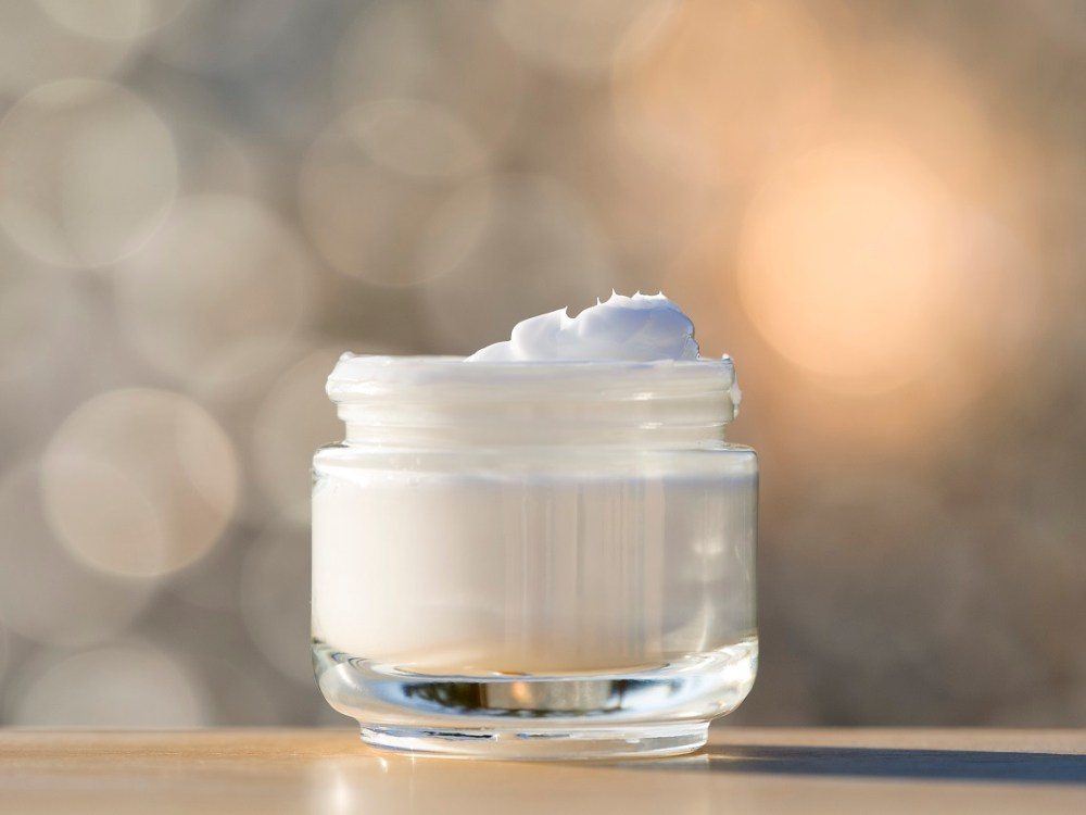 Glass jar of moisturizer for the body open, lit by sunlight