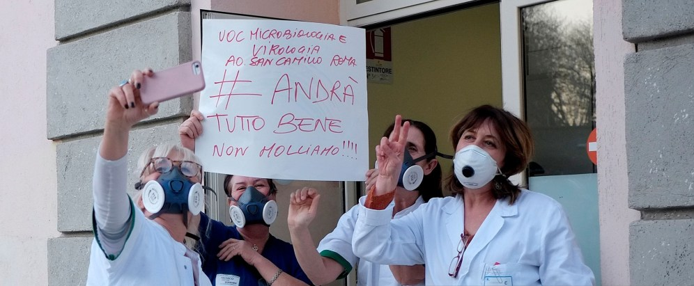 "ROME, ITALY - MARCH 16: Medical nursing and technical staff of the UOC Microbiology and Virology of San Camillo - Forlanini Hospital step out with protective masks singing ""Volare"" in the usual flash mob at 6 pm against the coronavirus and to encourage and give hope, and display a sign that says ""Everything will be fine, don't give up!"" on March 16, 2020 in Rome, Italy. The Italian Government has adopted the measure of a national lockdown by closing all activities, except for essential services such as pharmacies, grocery stores, hardware stores, tobacconists and banks, in an attempt to fight coronavirus (COVID-19). Movements are allowed only for reasons of work, health and necessity. Citizens are obliged to respect the safety distance of one meter from each other in line in supermarkets or public spaces. (Photo by Simona Granati - Corbis/Corbis via Getty Images)"