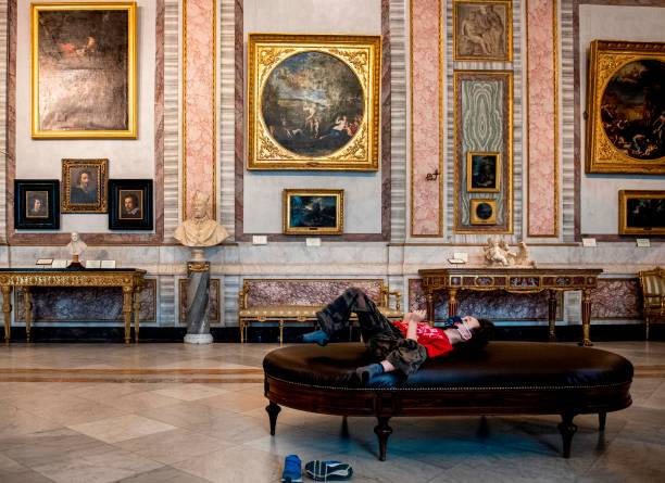 A child lays on a sofa at the Galleria Borghese museum in Rome on May 19, 2020, as it reopens while the country's lockdown is easing after over two months, aimed at curbing the spread of the COVID-19 infection, caused by the novel coronavirus. (Photo by Tiziana FABI / AFP) / RESTRICTED TO EDITORIAL USE - MANDATORY MENTION OF THE ARTIST UPON PUBLICATION - TO ILLUSTRATE THE EVENT AS SPECIFIED IN THE CAPTION (Photo by TIZIANA FABI/AFP via Getty Images)