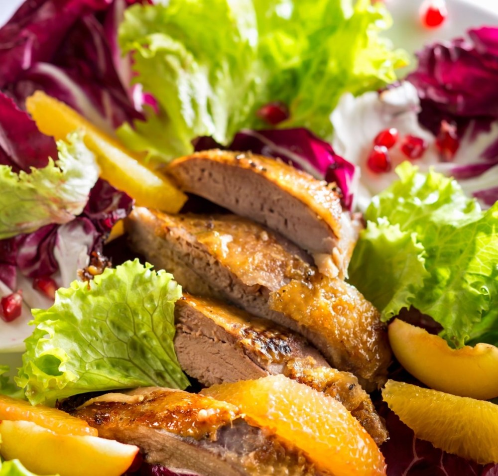 A colourful salad with duck breast, orange fillets and pomegranate seeds