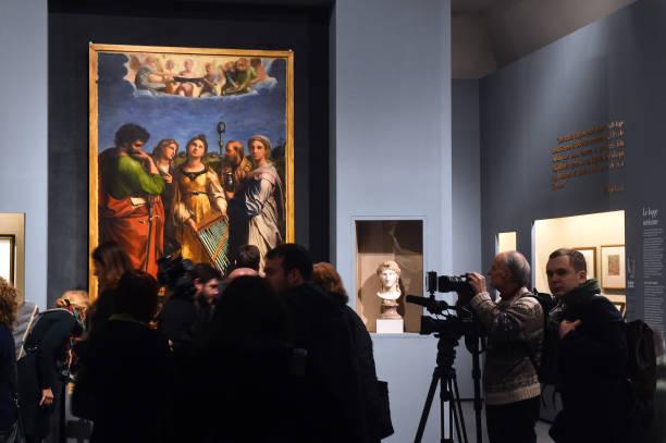 """ROME, ITALY - MARCH 04: Visitors admires the work """"Ecstasy of Saint Cecilia"""" by Raffaello Sanzio (Raphael) during the preview of the """"Raffaello"""" exhibition about italian artist of Rinascimento (Renaissance) Raffaello Sanzio (Raphael)at Scuderie del Quirinale on March 04, 2020 in Rome, Italy. (Photo by Roberto Serra - Iguana Press/Getty Images)"""