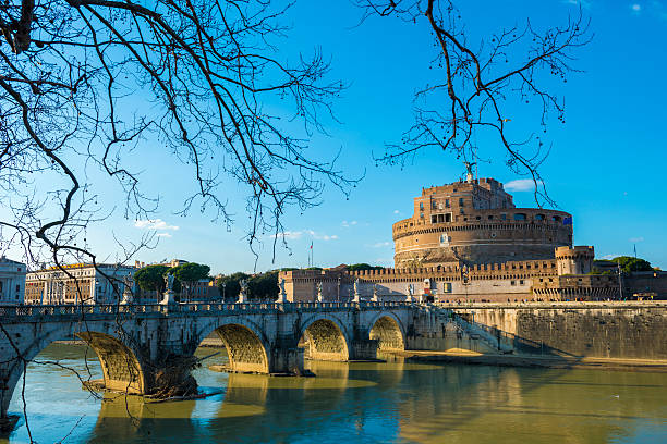 [UNVERIFIED CONTENT] Castle and bridge Sant'Angelo with tree branches and blue sky over Tiber river in Rome Italy