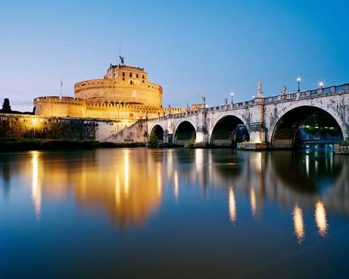 Pont Sant'Angelo and Castle Sant'Angelo reflected in River Tiber at dusk.