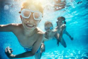 Happy kids having underwater party in the swimming pool. The boy is grinning at the camera. Shot with Nikon D850.