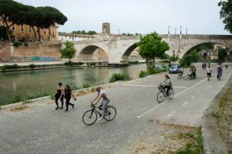People ride their bicycle on a bike lane along the Tiber river in front of Isola Tiberina in central Rome on May 16, 2020 during the country's lockdown aimed at curbing the spread of the COVID-19 infection, caused by the novel coronavirus. (Photo by Andreas SOLARO / AFP) (Photo by ANDREAS SOLARO/AFP via Getty Images)