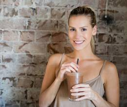 Young woman having a chocolate milkshake and looking very happy at a restaurant