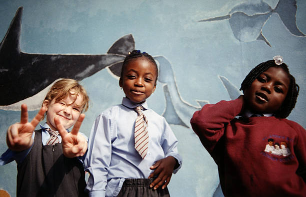 Group of school kids standing in front of a mural, one girl giving the peace sign, South London, UK, 2000s. (Photo by: PYMCA/Universal Images Group via Getty Images)