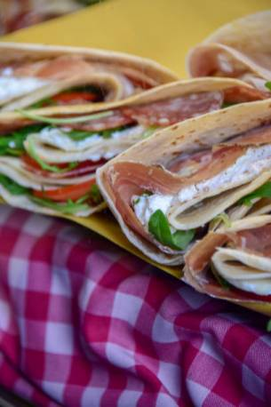 A piadina wrap filled with Italian Parma ham on display for sale at a food market
