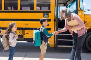 On his first day of school, a male child with a backpack on shakes the bus driver's hand outside the school bus.