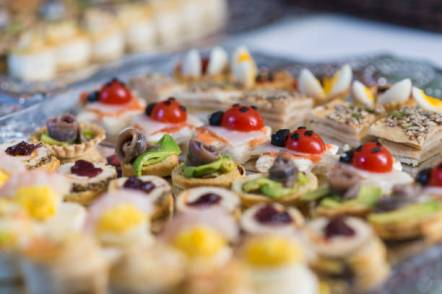 Low angle view and selective focus of haute cuisine canapes, with different shapes and colors, served in rows on a tray to celebrate Christmas dinner at home. Madrid, Spain.
