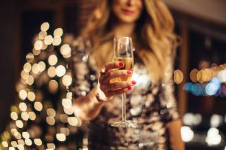 Close up of woman's heands holding glass of champagne. Woman wearing sparkly elegant dress. Evening or night with Christmas tree in background.