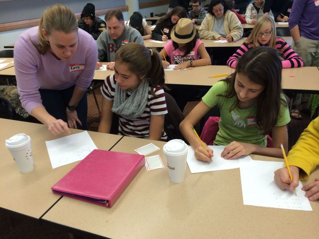 """Katharine Ott (standing) leads the group through the """"Four Numbers Game""""."""