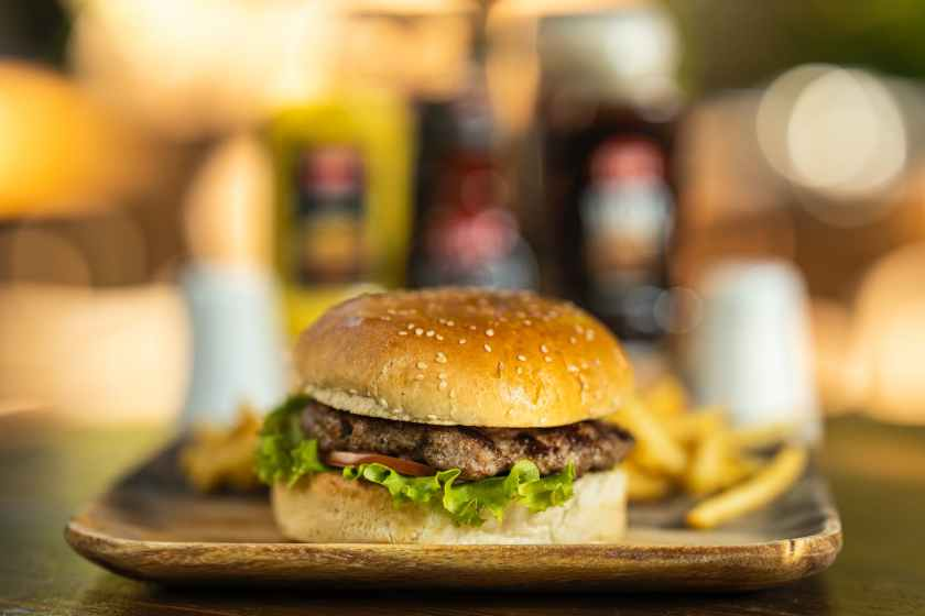 selective focus photography of hamburger with patty and lettuce on plate