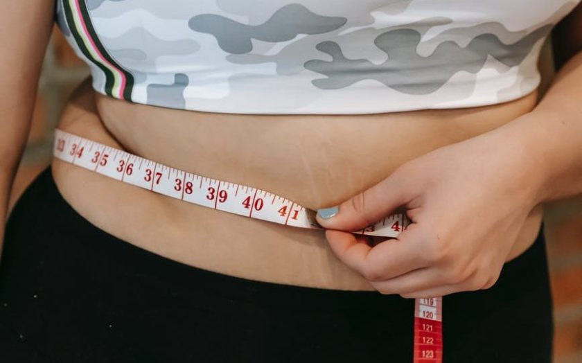 plus size woman using measuring tape on belly