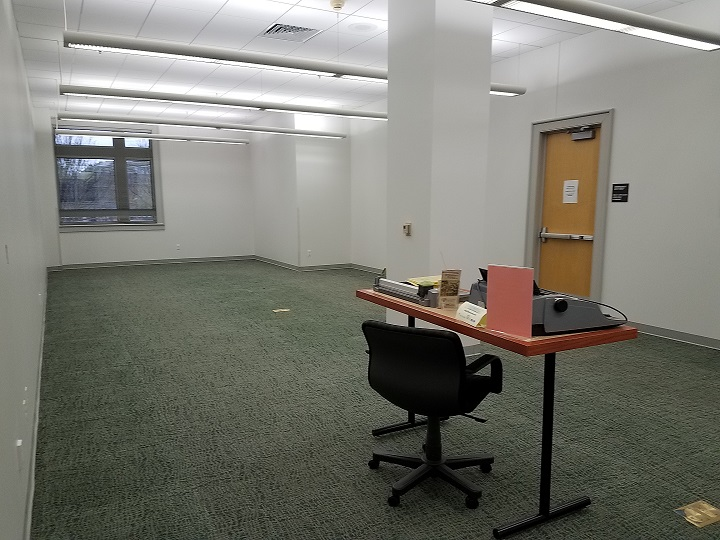 An empty room 129 where the library's collection of microfilm and microfiche used to be.