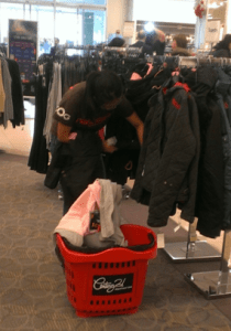 A customer searches for a coat size at Century 21, which was relatively slow on Black Friday. Photo by Dale Kim