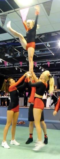 Cheerleaders holding up another cheerleader.