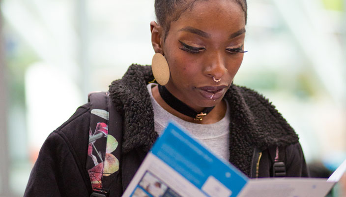 A female student reading the Open Day programme schedule
