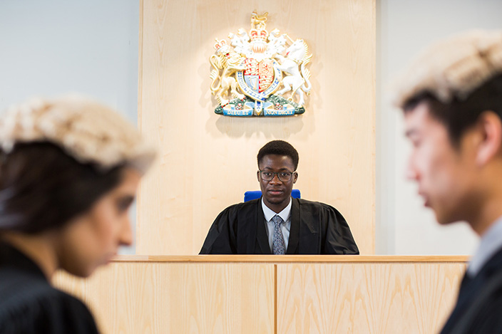 Three students using the University's Lady hale mock courtroom.