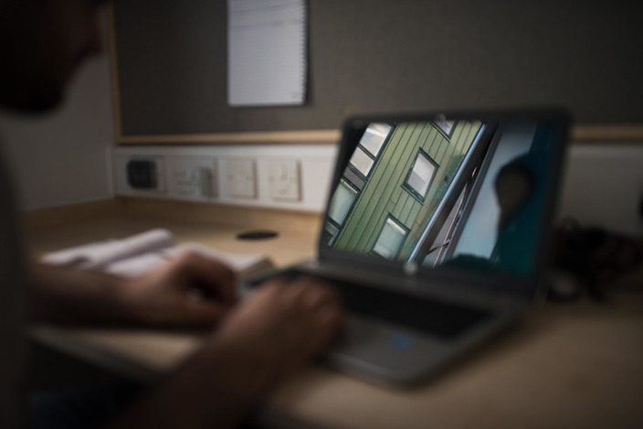 A student sat at a desk, using a laptop in their campus accommodation bedroom.
