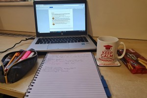 A student's desk with a laptop, pencil case, notepad, mug and coaster on it.