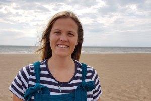 Headshot of Maria stood on an empty beach.