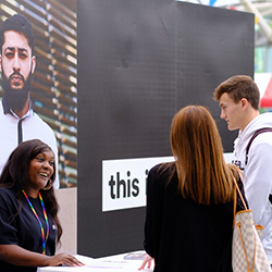 Two prospective students chatting to a member of staff at an Open Day.