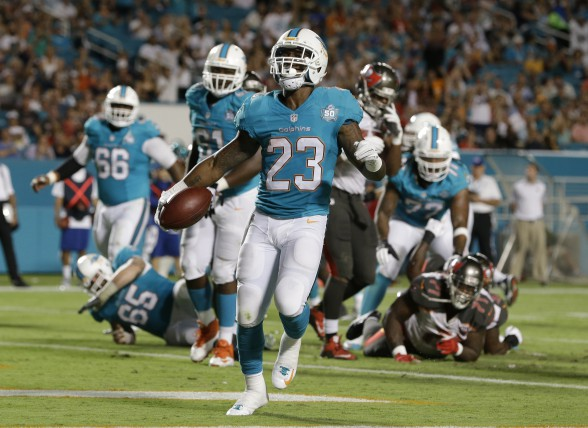 Miami Dolphins running back Mike Gillislee (23) celebrates a touchdown during the first half of an NFL preseason football game against the Tampa Bay Buccaneers, Thursday, Sept. 3, 2015, in Miami Gardens, Fla. (AP Photo/Wilfredo Lee)