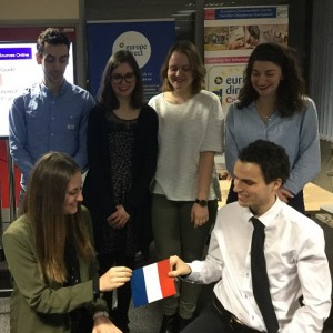 Two people holding a French flag, with four people standing behind them.