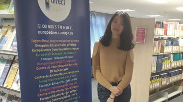 Carol Zhang standing next to a Europe Direct banner.