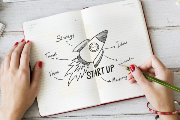 Women drawing a start-up rocket