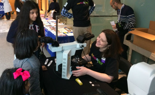 Children looking at microscope at See, Test & Treat event at Montefiore