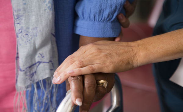 portrait of hands. one hand holding a walker and another on top of that hand in a caring gesture
