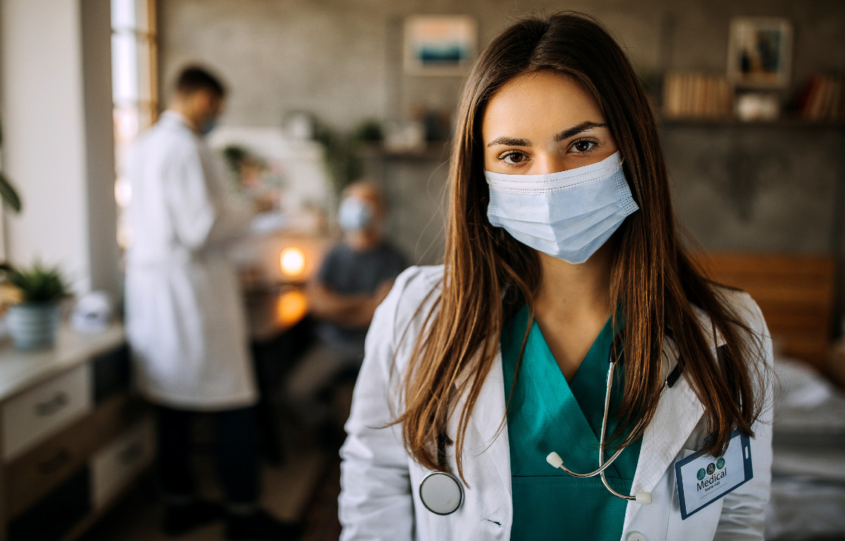 Young woman doctor wearing mask looking at camera with other doctors (blurry) talking in background