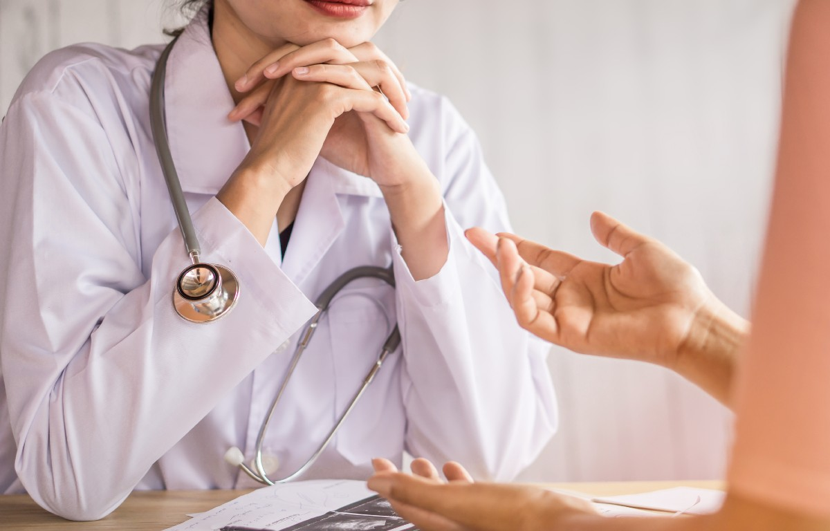 doctor listening to someone speak. doctor facing camera only shown mouth down. hands raised to chin elbows on table. only hands of other person shown