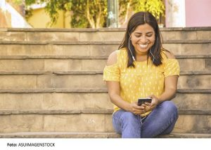 thumbnail_asuimagenstock_happy woman using mobile in the street