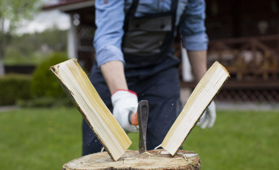 close-up-lumberjack-chopping-wood-with-ax-sawdust-fly-to-sides-harvesting-wood