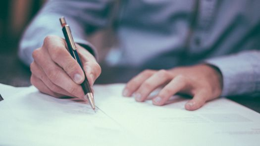 A man is seen signing a bunch of papers.