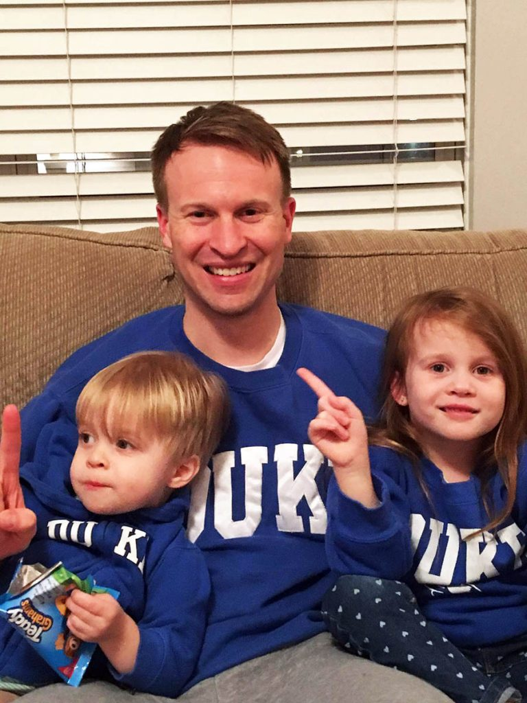 Jamie on a sofa with his two small kids and all are wearing Duke sweatshirts; family life